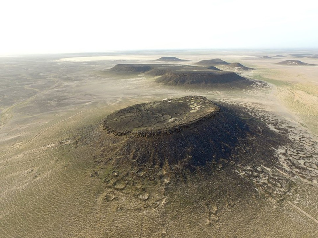 "Mesa M-4 (""Maitland's Hillfort"") in the Wadi al-Qattafi in the Black Desert. Numerous Late Neolithic dwellings and corrals are located on the slopes and foot of the mesa, and possible Early Bronze Age terraced garden plots are located on the summit. (Photo: A.C. Hill)."